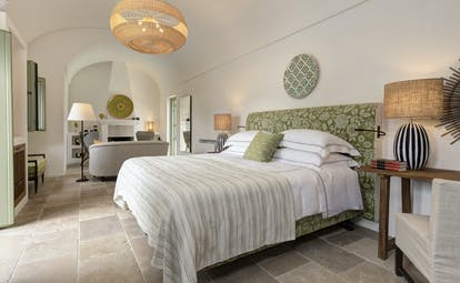 Pale bedroom with sitting room and stone floor at Torre Maizza