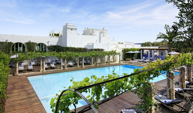 White square building with outdoor pool and sun deck at Torre Maizza