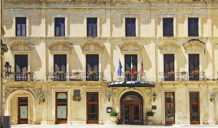 Facade in beige stone with long windows on three floors of the Patria Palace Lecce