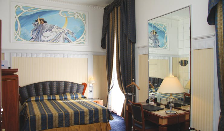 Bedroom at the Patria Palace Lecce with blue and brown striped bedspread