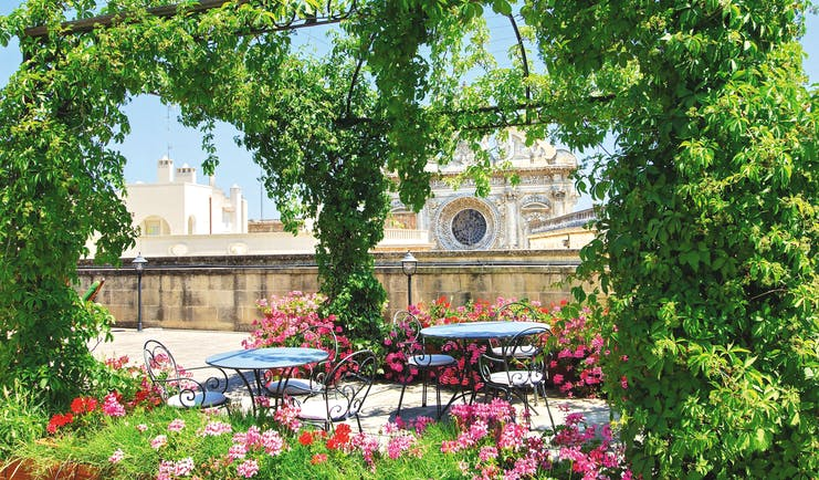 Patria Palace Puglia rooftop terrace outdoor dining area canopy of vines pink flowers