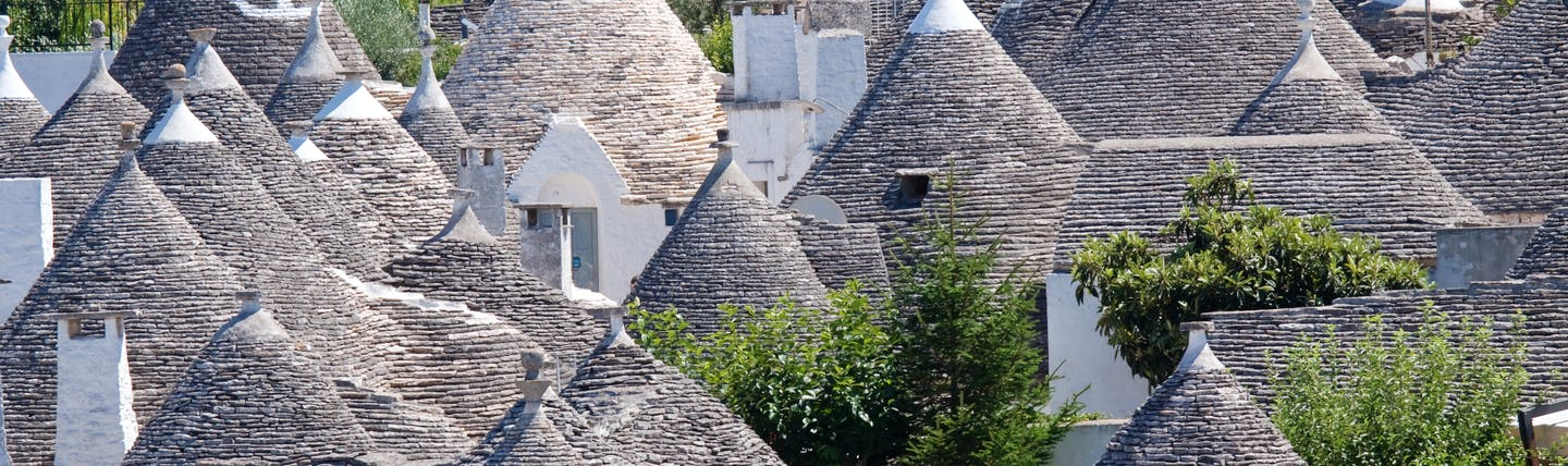 Conical grey slate roofs of the Trulli houses clustered together in Alberobello Puglia