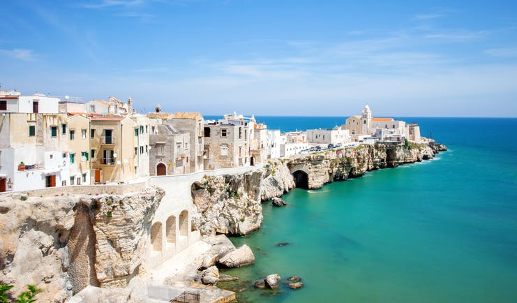 Line of white houses on white cliffs above emerald sea at Vieste in Puglia