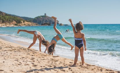 Three kids playing on the sandy beach with the the blue sea behind them and cliffs in the background