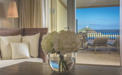 Inside the living space of a deluxe room at the Chia Laguna with white flowers on the coffee table and doors opening up onto a terrace balcony overlooking the sea