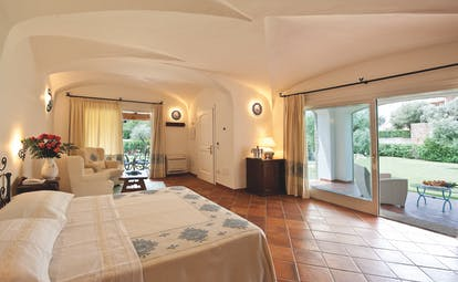 La Rocca Sardinia deluxe suite bedroom living area terrace overlooking garden modern décor