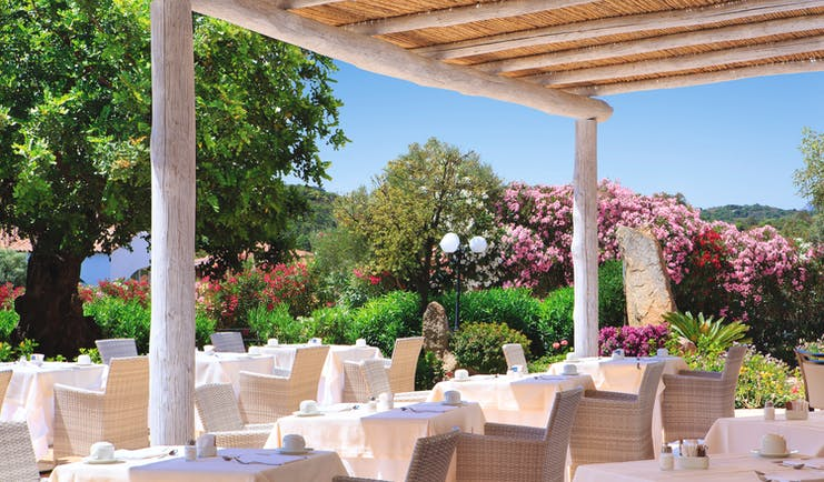 La Rocca Sardinia outdoor dining restaurant surrounded by trees flowering bushes