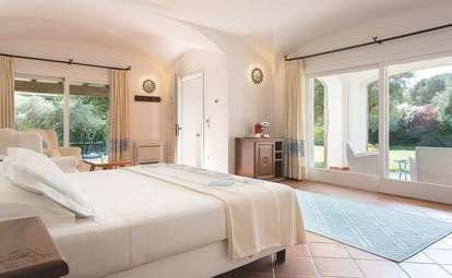 La Rocca Sardinia villa del parco junior suite living area bed patio doors leading to garden