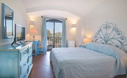 Hotel Le Ginestre Sardinia guestroom, double bed, chest of drawers, doors leading to balcony with garden view