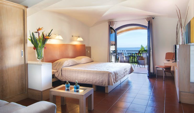 Hotel Le Ginestre Sardinia junior suite, double bed, living area, doors to private balcony with sea view