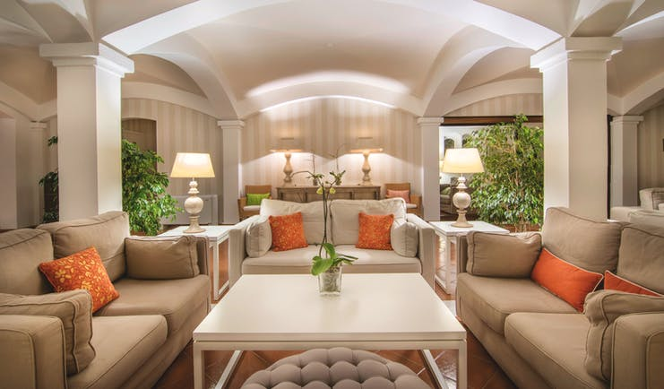 Hotel Le Ginestre Sardinia lobby, communal seating area, large white sofas, bright elegant decor