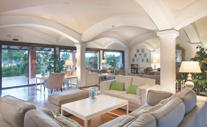 Hotel Le Ginestre Sardinia lounge, communal seating area, large white sofas, french windows opening onto garden, bright elegant decor