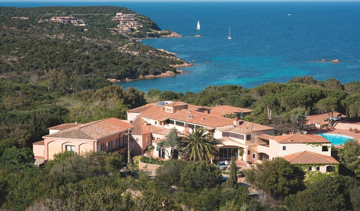 Hotel Le Ginestre Sardinia resort, hotel buildings nestled on wooded coastline, sea and beach in background