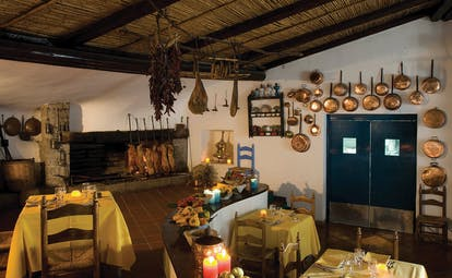 Restaurant with pots and pans for decoration, and tables set out for dinig
