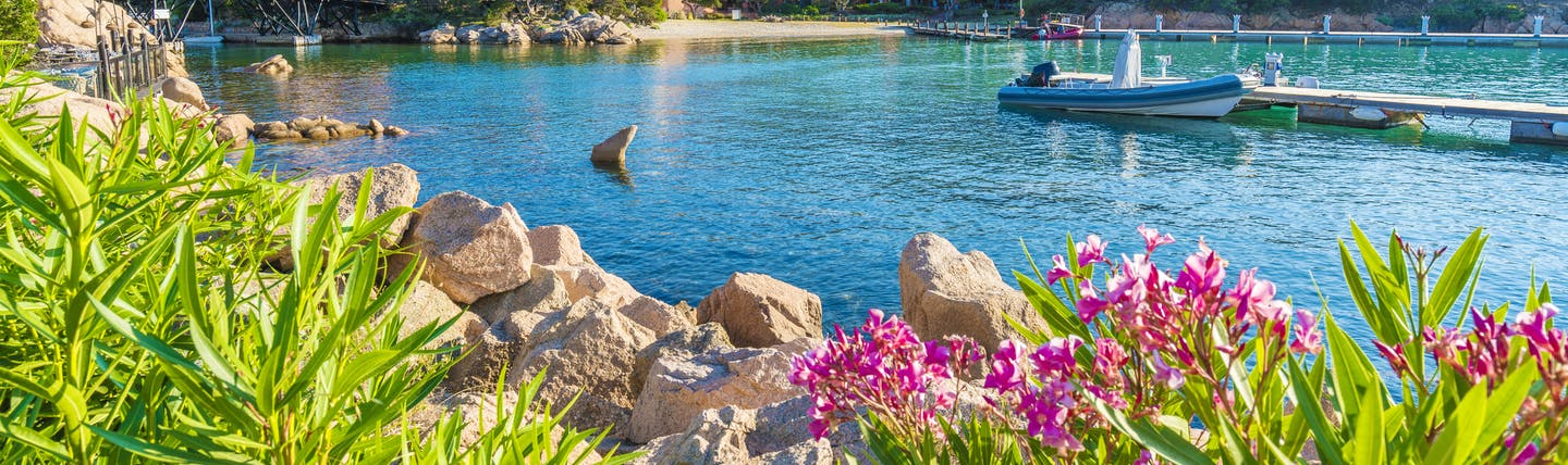 Turquoise calm sea flanked by pink hibiscus flowers in Porto Cervo Sardinia