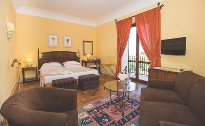 Baglio Oneto deluxe room, double bed, armchairs and sofa, tiled floor, balcony with garden views, bright traditional decor