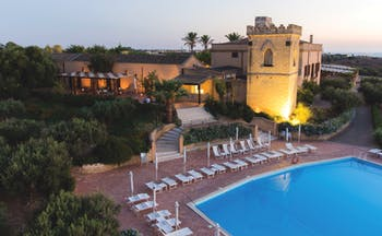 Baglio Oneto pool, pool deck with sun loungers, hotel building in background, traditional architectural features