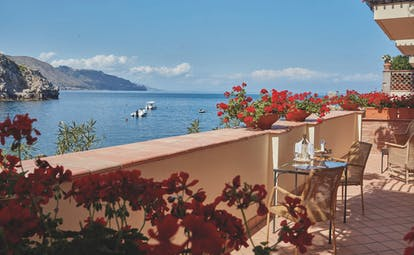 Villa Sant Andrea Sicily balcony outdoor seating area red flowers sea views