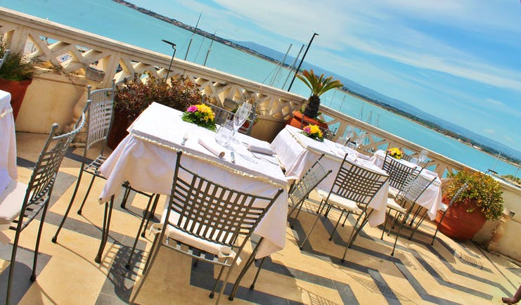 Dining area on the terrace looking over the sea with tables and chairs set up for dining