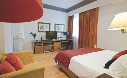 Deluxe double room with a red and white colour scheme, a large double bed, television and armcahir