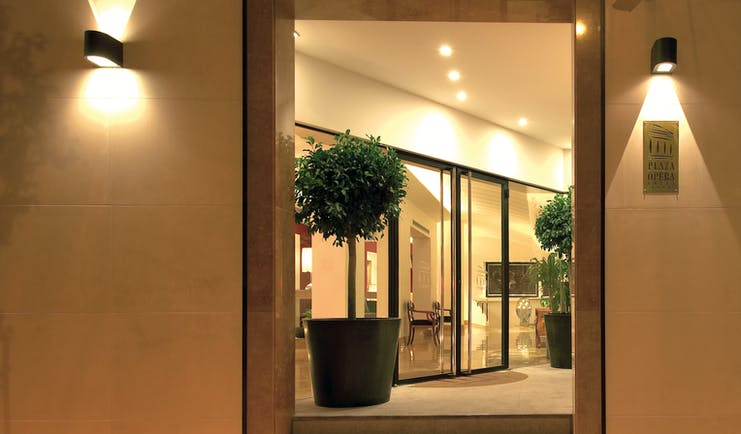 View of the entrance of the Hotel Plaza Opera with plants shown surrounding the doors