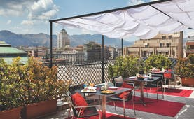 View from the rooftop terrace of Hotel Plaza Opera looking over the plaza, with red rugs and dining tables set out beneath a white veranda and amongst potted plants