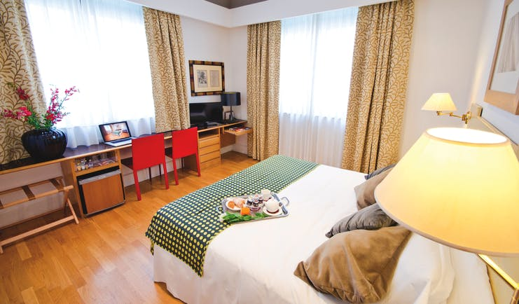 standard double room at the Hotel Plaza Opera, with a green colour scheme, including a double bed, desk and television