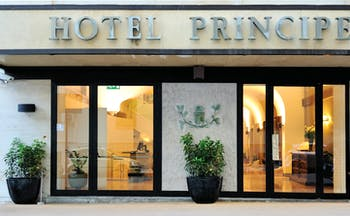 Hotel Principe di Villafranca entrance, hotel name, glass doors, lit up lobby