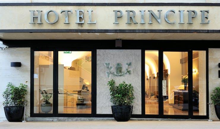 Hotel Principe di Villafranca entrance, hotel name, glass doors, lit up lobby
