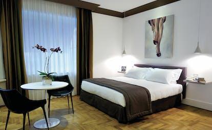 Hotel Principe di Villafranca junior suite, double bed, tables and chairs, wooden floor, bright modern decor