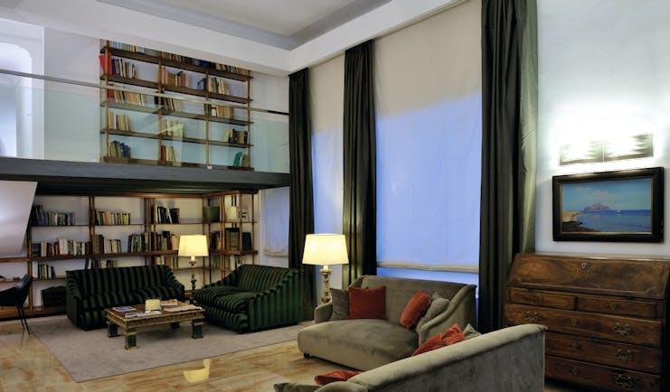 Hotel Principe di Villafranca library, communal seating area, bookshelves, low velvet sofas, elegant decor