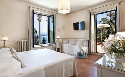 Hotel Villa Belvedere Sicily terrace suite bedroom sofa doors leading to terrace side view of ocean