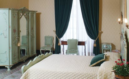 Double room with chandelier, large double bed and draping velvet curtains