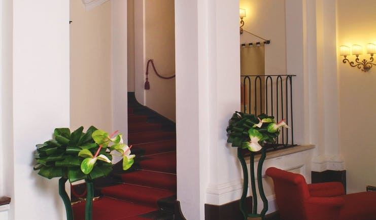 Hallways area with red carpet, white arching pillars and potted plants