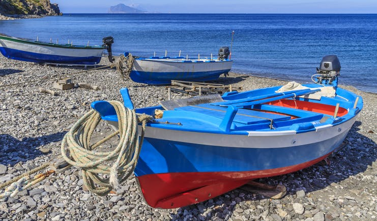 Red and blue fishing boat on pebble beach on Lipari in the Sicilian Aeolian Islands