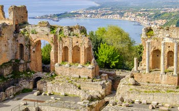 Columns and arches of the Greek theatre in taormina with sea behind