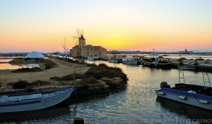 Sunset view of windmill by sea