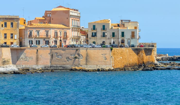 White and yellow buildings built into stone walls above the sea on the island of Ortigia in Sicily