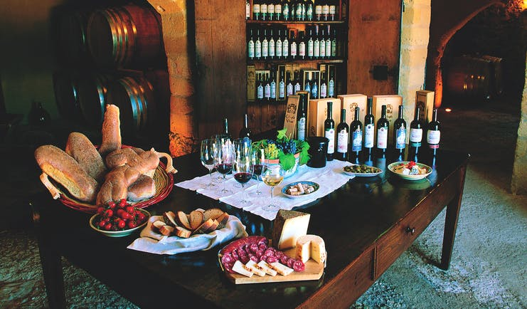 Bottles of wine and cold cuts and bread for tasting on table
