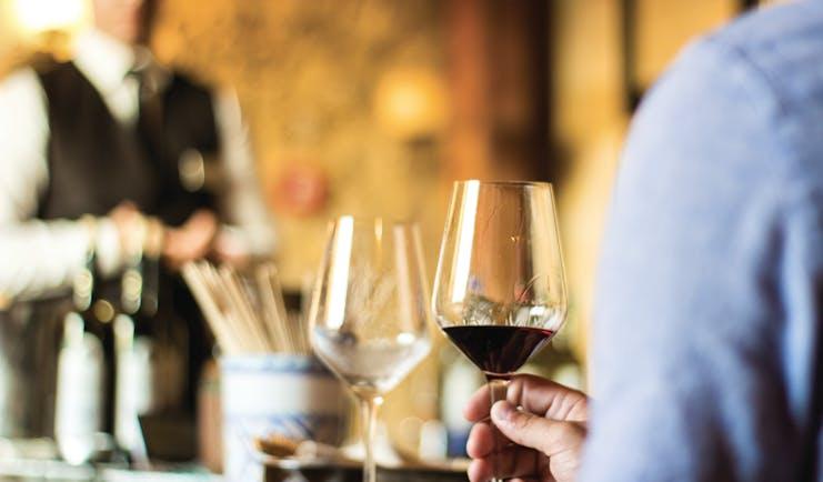 Waiter with wine bottles and glasses for tasting