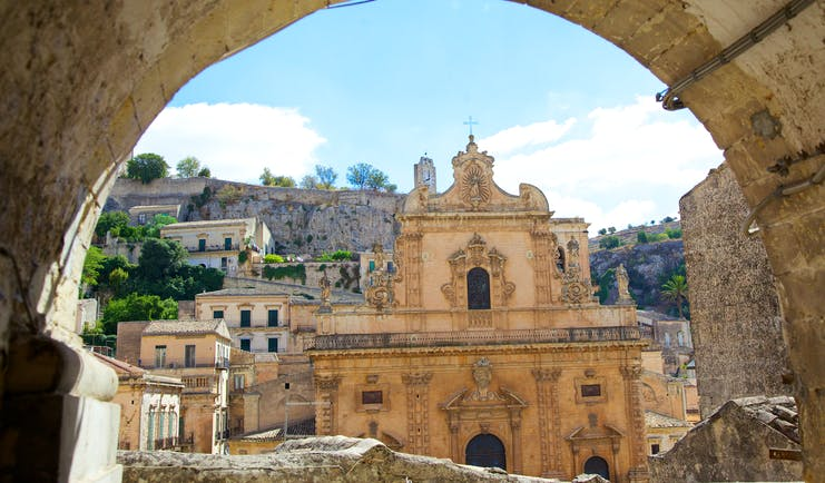 Baroque front of the cathedral of St Peter through a stone arch in Modica Sicily