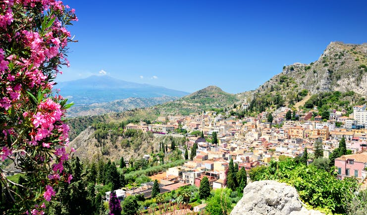 Pink flowers in foreground with town of Taormina and Mount Etna volcanic dome in background in Sicily