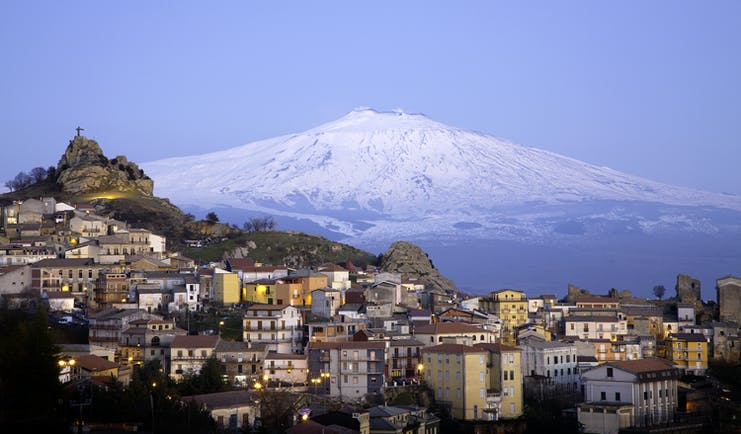 Snow capped Mount Etna with hilltop village of San Teodoro