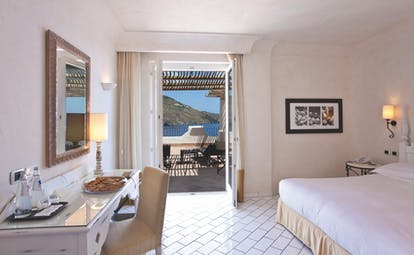Deluxe suite at the Therasia Resort with a white colour scheme, large white double bed, and double doors opening onto a terrace balcony