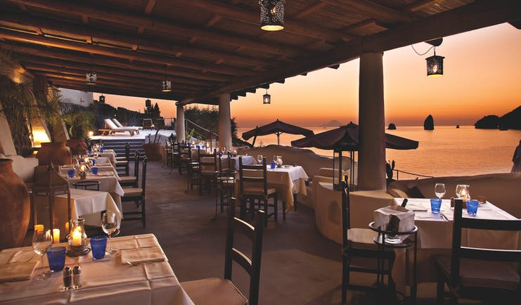 Therasia Resort Sicily dining terrace outdoor seating overlooking beach and Faraglione rocks