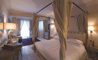 Junior suite at the Therasia resort in Sicily with a cream and yellow colour scheme and large double bed
