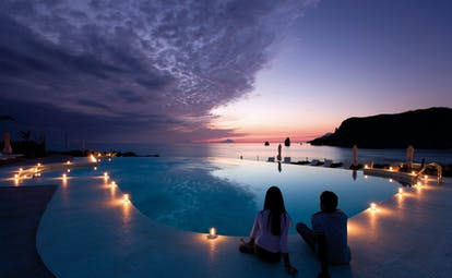 Pool at night with candles lit up around the edge of the pool and the sun setting over the sea in the distance