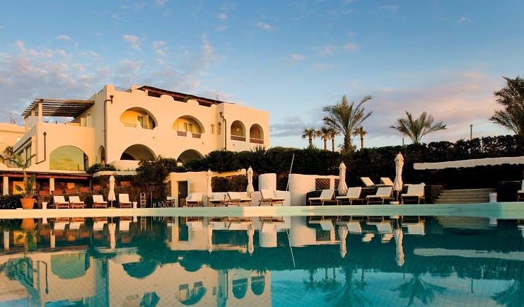 View of hotel exterior and pool infront with palm trees around and sun loungers