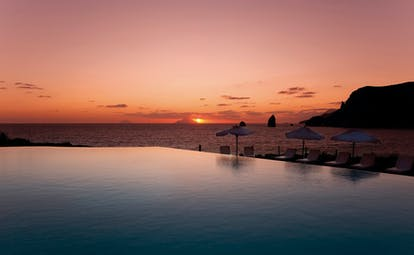 Pool sunset view with sun setting by the sea