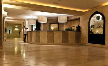 Reception area with beige colour scheme, dimly lit lights and stone walls and ceilings